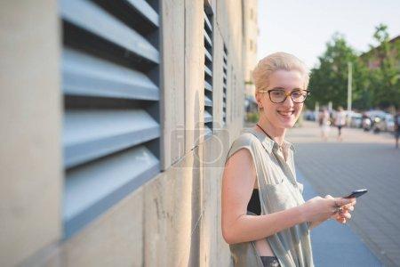 Foto de Mujer joven con smartphone mirando a cámara - tecnología, red social, concepto de felicidad al aire libre - Imagen libre de derechos