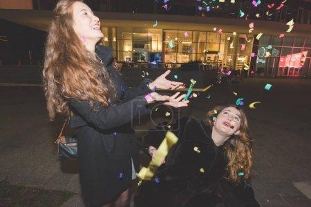 Photo pour Deux jeunes femmes en plein air nuit de ville jouer avec confettis - célébrer, fête, ayant concept amusant - image libre de droit