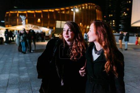 Photo pour Deux jeunes amies marchant en plein air la nuit s'amuser - bonheur, puissance des filles, concept d'interaction - image libre de droit