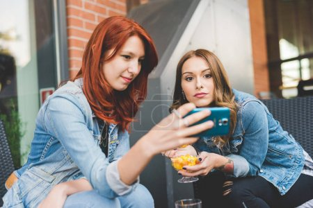 two young women outdoor using smart phone having fun - technology, social network, communication concept