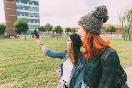 Foto de Dos mujeres caminando al aire libre tomando selfie utilizando teléfonos inteligentes - interacción, concepto de tecnología - Imagen libre de derechos