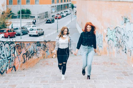 two young women walking outdoors having fun hand in hand - interaction, happiness, friendship concept