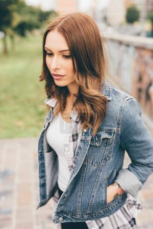 young woman outdoors posing looking away - pensive, serious, serene concept
