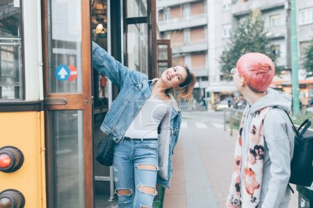 Photo pour Deux jeunes femmes descendant du tram en plein air - image libre de droit