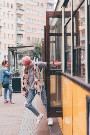 Photo pour Jeune femme cheveux roses dehors descendant du tram - image libre de droit