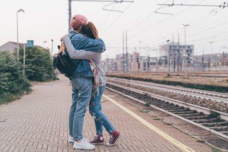 Photo pour Deux jeunes femmes en plein air embrassant la gare - adieu, départ, tristesse concept - image libre de droit