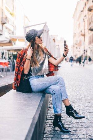 Photo pour Jeune femme en plein air utilisant un téléphone intelligent - vanité, réseau social, concept de partage - image libre de droit