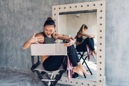 Photo pour Jeune femme à l'intérieur assise chaise du directeur regardant ailleurs - attitude, blogueur, concept d'influence - image libre de droit