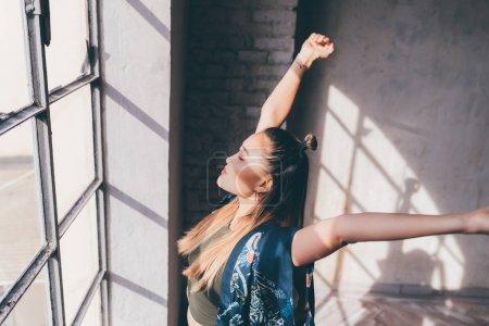 Photo pour Une jeune femme à l'intérieur étire les bras debout devant une fenêtre - renoncer au concept paisible et détendu - image libre de droit