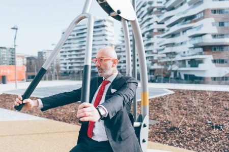 Middle age contemporary businessman working out on outdoor sports facilities