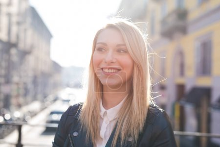Portrait young woman beautiful blonde hair outdoor looking away, smiling
