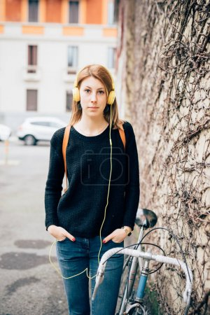 Photo for Young beautiful woman with bicycle leaning on wall looking camera listening music - Royalty Free Image