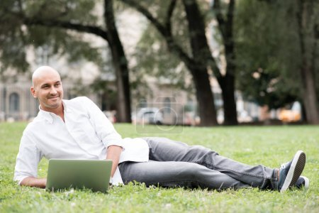 Young contemporary businessman remote working lying down outdoor in a city park using computer