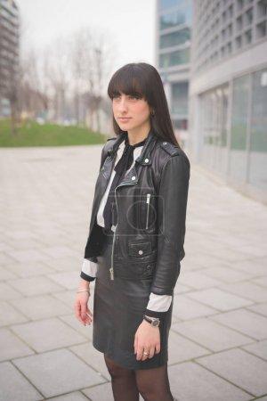 Photo pour Fille de jeunes beaux cheveux brun caucasien posant marchant dans les rues de la ville, donnant sur - image libre de droit