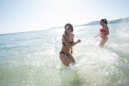 Photo pour Amies milléniaux portant maillots de bain éclaboussant autour d'avoir du plaisir - image libre de droit