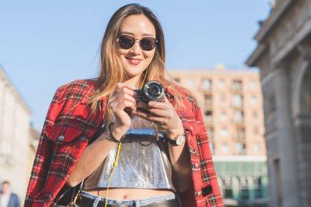 Photo pour Jeune femme en plein air à l'aide de la caméra - photographe, concept créatif, émotions positives - image libre de droit