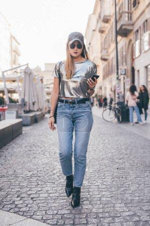 Photo pour Une jeune femme se promène à l'extérieur en regardant le téléphone intelligent - voyageuse, influenceuse, concept de blogueur - image libre de droit