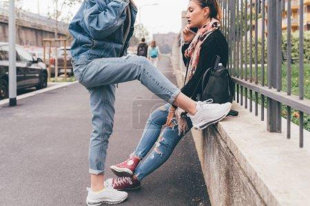Photo pour Section du milieu deux jeunes femmes à l'extérieur en utilisant le téléphone intelligent - en ligne, la culture des jeunes, concept de réseau social - image libre de droit