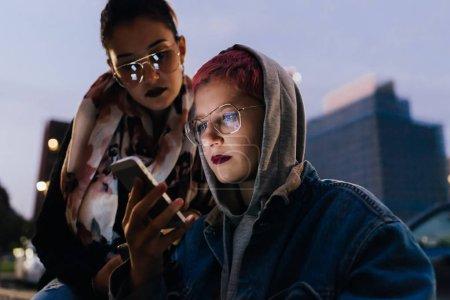 Photo pour Deux jeunes femmes en plein air dans la nuit en utilisant la lumière de l'écran éclairé visage de téléphone intelligent - en ligne, culture de la jeunesse, concept d'Internet - image libre de droit