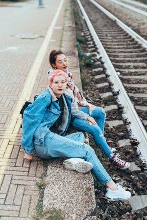 Photo pour Deux jeunes femmes assises à la gare regardent la caméra - meilleurs amis, liens affectifs, concept d'interaction - image libre de droit