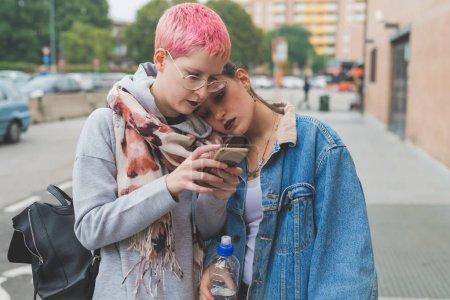Photo pour Deux jeunes femmes utilisent le téléphone intelligent à l'extérieur - en ligne, culture des jeunes, concept de réseau social - image libre de droit