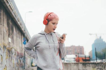 Photo pour Une jeune femme aux cheveux roses écoute de la musique à l'extérieur avec des écouteurs à l'aide d'un téléphone intelligent - détente, plaisir, concept technologique - image libre de droit
