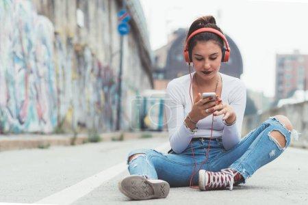 Photo pour Une jeune femme écoute de la musique en plein air avec des écouteurs à l'aide d'un téléphone intelligent - détente, plaisir, concept technologique - image libre de droit