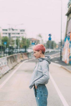 Photo pour Jeune femme aux cheveux roses en plein air posant en regardant ailleurs - blogueur, concept d'influence - image libre de droit