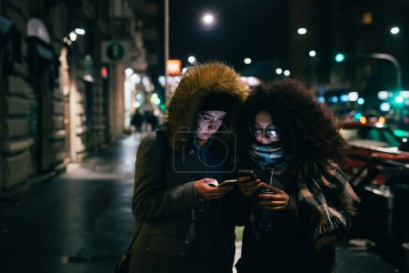 Photo for Two young women multiethnic outdoor using smart phone outdoor at night - phubbing, social network, communication concept - Royalty Free Image