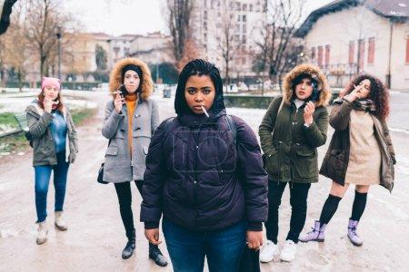 Photo pour Five young women multiethnic outdoor posing smoking cigarette - rebel, unhealthy, attitude concept - image libre de droit