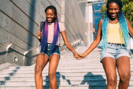 Photo pour Deux belles jeunes sœurs noires marchant ensemble en bas, tenant la main - la famille, la camaraderie, le concept d'attachement - image libre de droit