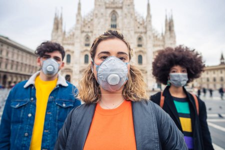 Photo for Three multiethnic friends wearing medical mask protecting from pollution and virus - anti-smog, infection, protester concept - Royalty Free Image