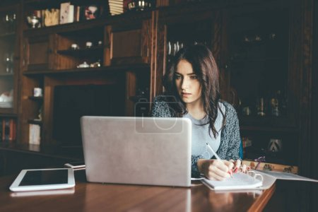 Photo for Young beautigul middle eastern woman indoor at home using computer writing on notebook - smart learning, smart working, business oncept - Royalty Free Image
