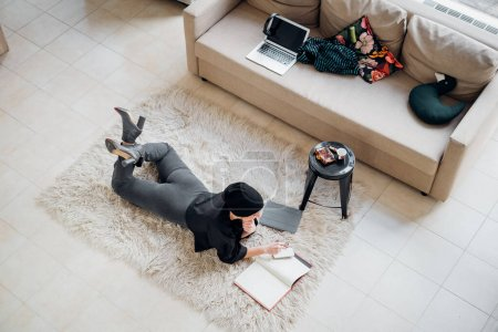 Photo for Top view adult woman indoor lying on carpet indoor at home using smartphone writing notebook - smart working, planning, freelancer concept - Royalty Free Image