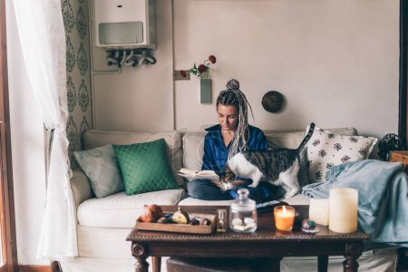 Photo for Adult woman indoors at home sitting couch reading book with friend cat - bookworm, quality time, mindfulness concept - Royalty Free Image