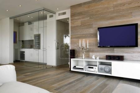Photo pour Vue intérieure d'un salon modern avec des lambris en bois, tlevision et plancher en bois surplombant sur la cuisine - image libre de droit