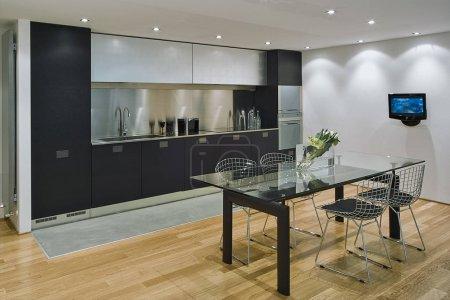 Photo pour Intérieurs plans d'une cuisine moderne au premier plan la table à manger en verre et chaises en fer le sol est en bois - image libre de droit
