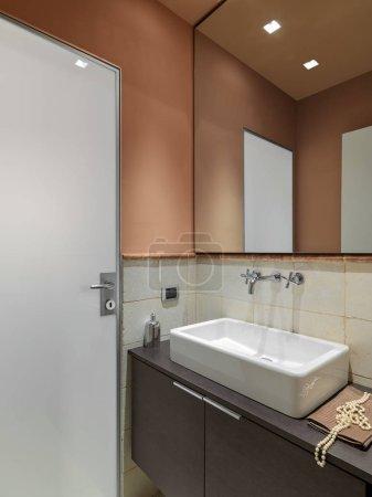 Photo pour Gros plan d'un lavabo de comptoir en céramique avec son robinet sur l'armoire en bois avec un grand miroir au-dessus, les murs sont teintés d'orange dans la salle de bain moderne - image libre de droit