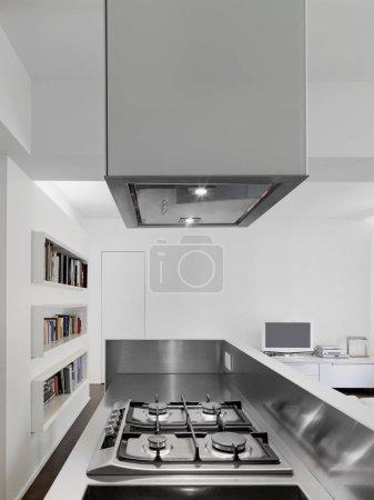 Photo pour Vue intérieure d'un appartement moderne au premier plan la plaque de cuisson au gaz d'une cuisine ouverte sur le salon - image libre de droit