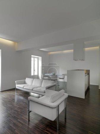 Photo pour Vue intérieure d'un appartement moderne au premier plan les canapés en tissu blanc sur la boulangerie thery sont la cuisine isalnd une table à manger en verre et ses chaises le sol est en bois - image libre de droit