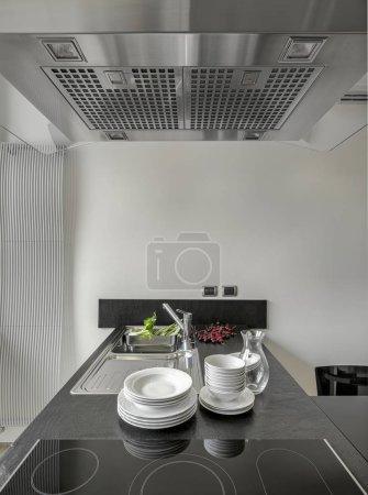 Photo pour Au premier plan, quelques assiettes blanches empilées sur le plan de travail près de l'évier dans la cuisine moderne sur fond de cerises et dans l'évier quelques légumes tandis que sur le plan de travail près d'eux il y a un peu de cerises - image libre de droit