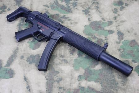 submachine gun MP5 with silencer on camouflaged background