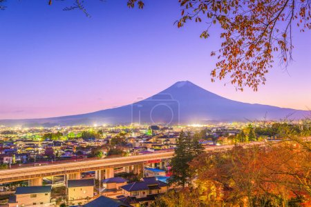 Fujiyoshida, Japan town skyline below Mt. Fuji at twilight during autumn season.