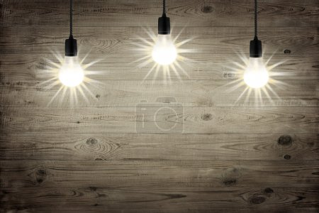 Three lightbulbs shining over brown wood texture background