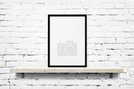 Photo for White blank photo frame mockup on shelf over white brick wall background - Royalty Free Image