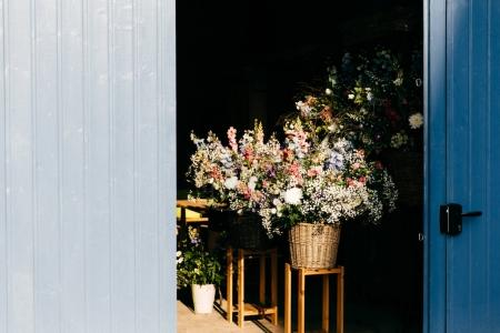 Beautiful flowers with pleasant smell in wooden backet. Bouquet of beautiful flowers with nice odour standing on chair in wooden backet. Blooming flowers