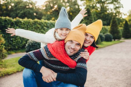 Having nice time together! Smiling excited woman, man and their little female child, wear warm knitted clothes, embrace each other, walk in park, being in good mood. Family give support, encouragement