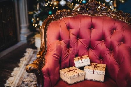 Horizontal picture of wrapped three gift boxes on beautiful royal armchair indoors. Home interior. Celebration, holidays, present concept. Christmas presents decorated with ribbons
