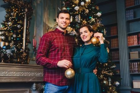 Handsome man with stubble embraces his beautiful wife, hold glass balls in hands, decorate New Year tree together, prepare for holidays. Smiling young beautiful female and her husband at home