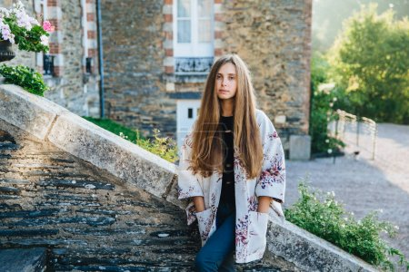 Young cute lovely woman stands against ancient beautiful city`s landmarks, wears mantel, has excursion with friends, finds out historical facts about town, looks directly at camera, serious expression